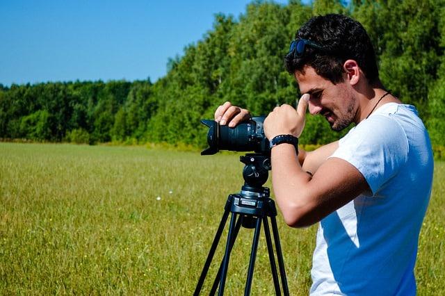 homme utilisant un trepied d'appareil photo